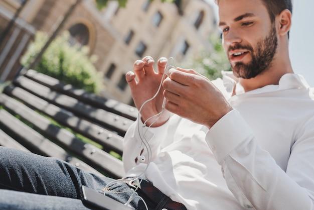 Soms is het meest productieve wat je kunt doen, ontspannen, knappe man houdt zijn oortelefoons vast