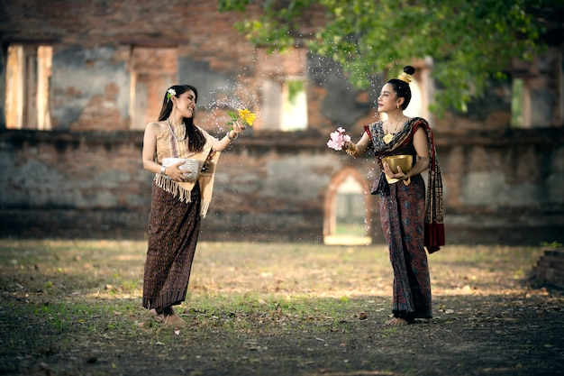 Songkran-festival. een vrouw in thaise klederdracht spettert water op het songkran-festival, een thaise nationale traditie, die wordt beschouwd als het thaise nieuwjaar.