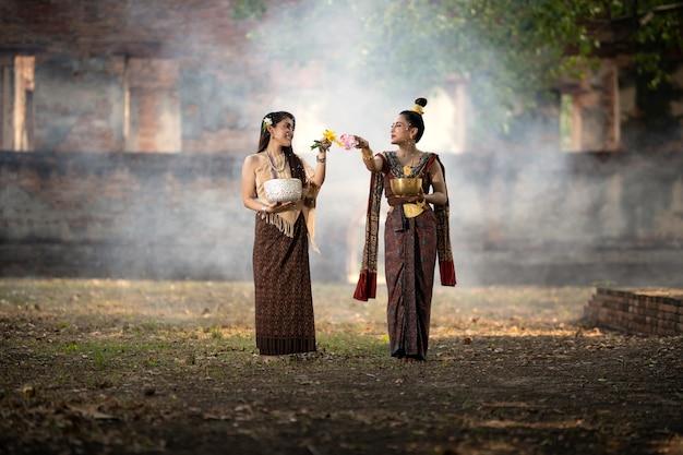 Songkran-festival. het meisje in thaise klederdracht spettert water op songkran day.