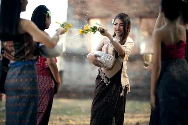 Songkran festival veel jonge vrouwen in thaise klederdracht spetteren water op songkran day.