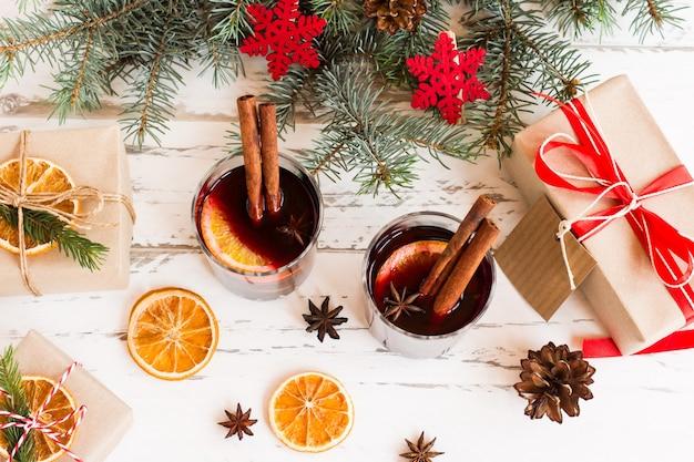 Sony dscmulled wijn in wit geëmailleerde mokken met kruiden en citrusvruchten op houten tafel met pelsboomtakken en kerstcadeaus