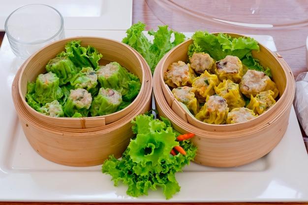 Soort chinese snacks, chinees gestoomd dimsum in bamboe met groene en gele kleuren.