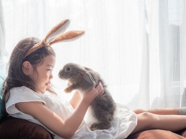 Soort klein schattig meisje 5-6 jaar oud zitten en houden van een grijs konijn in de buurt van het venster.