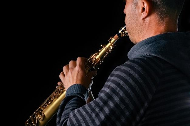 Sopraansaxofoon in de handen van een man op een zwarte achtergrond