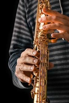 Sopraansaxofoon in de handen van een man op een zwarte ondergrond