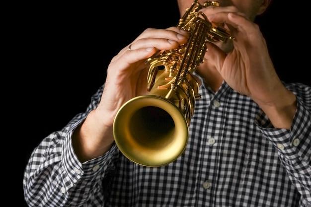 Sopraansaxofoon in handen op een zwarte ondergrond