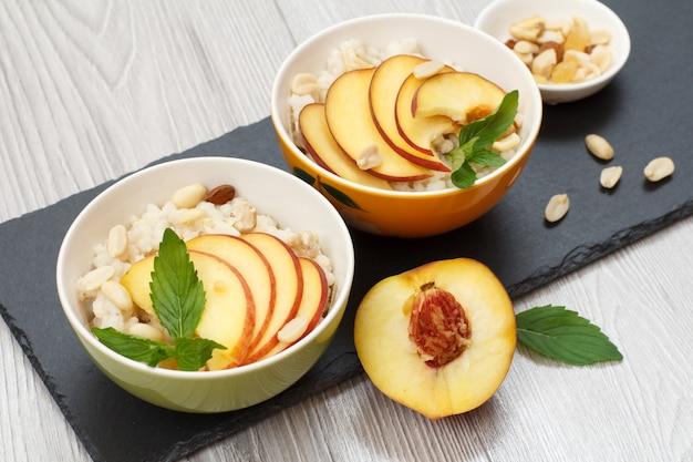 Sorghumpap met perzik, cashewnoten, amandel- en muntblaadjes in porseleinen kommen op zwart stenen bord. vegan glutenvrije sorghumsalade met vers fruit. bovenaanzicht.