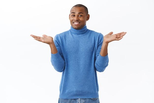 Sorry weet het niet. portret van een onwetende afro-amerikaanse man, schouderophalend en glimlachend, kan het niet zeggen, heeft geen antwoorden