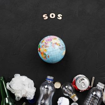 Sos-brieven, aarde en stapel afval op donkere achtergrond