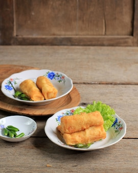 Sosis solo, kipgehakt met ei crêpe wrap en vorm als worst. meestal geserveerd met thee, groene chilipeper en chilisaus. solo centraal java typisch eten.