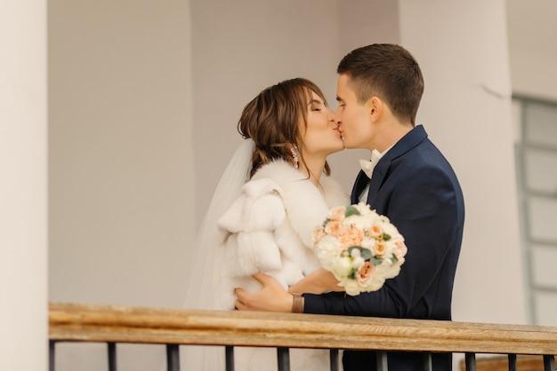 Soulful foto van de pasgetrouwden knuffelen en zoenen. bruiloft fotografie van stijlvolle bruid en bruidegom.