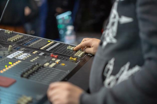 Soundman werkt aan de mengtafel. de hand beweegt één schuifregelaar.