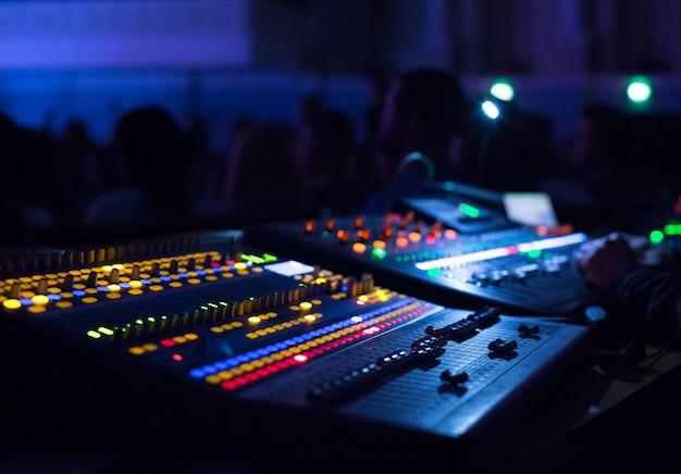 Soundman werkt aan de mengtafel in concertzaal. handen op de schuifregelaars.