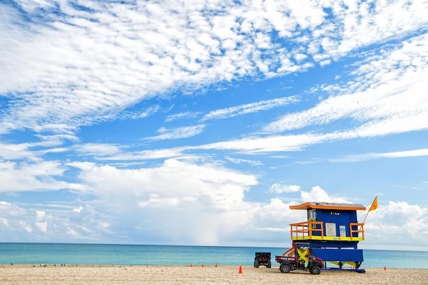 South beach, miami, florida, badmeesterhuis in een kleurrijke art deco-stijl op bewolkte blauwe hemel en de atlantische oceaan op de achtergrond, wereldberoemde reislocatie