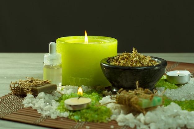 Spa-accessoires met zeep, kom met gedroogde kamillebloemen, flessen met aromatische olie, zeezout, kaarsen op bamboeservet