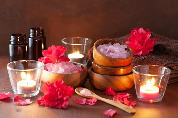 Spa aromatherapie met azalea bloemen en kruidenzout op rustieke donkere tafel