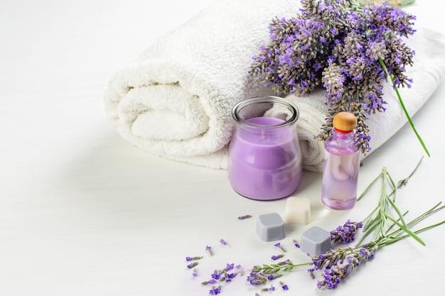 Spa aromatische producten. lavendelbloemen, kaars, zeep, huidolie en witte handdoeken. spa-aromatherapie, gezondheidszorgconcept.