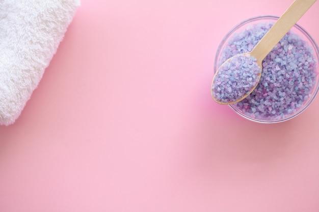 Spa. bad organisch zout op houten lepel op roze achtergrond met exemplaarruimte.
