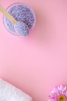 Spa. bad organisch zout op houten lepel op roze met copyspace.