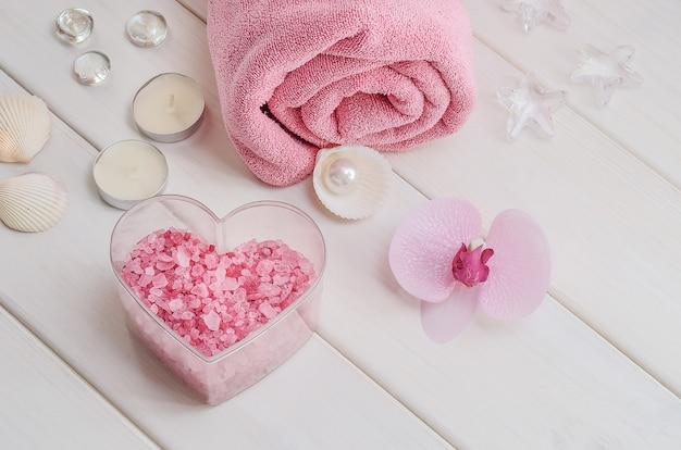 Spa-behandelingen als cadeau voor valentijnsdag. roze handdoek met bloem, schelpen en roze zeezout in de vorm van een hart op een witte houten ondergrond. schoonheidssalon, massage.