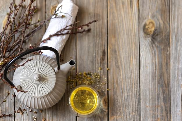Spa compositie in rustieke stijl met een theepot en thee op een houten oppervlak.