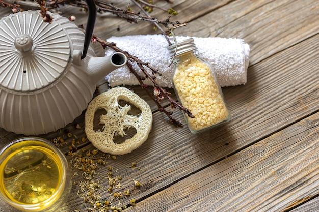 Spa compositie in rustieke stijl met waterkoker, thee en luffa op een houten oppervlak.