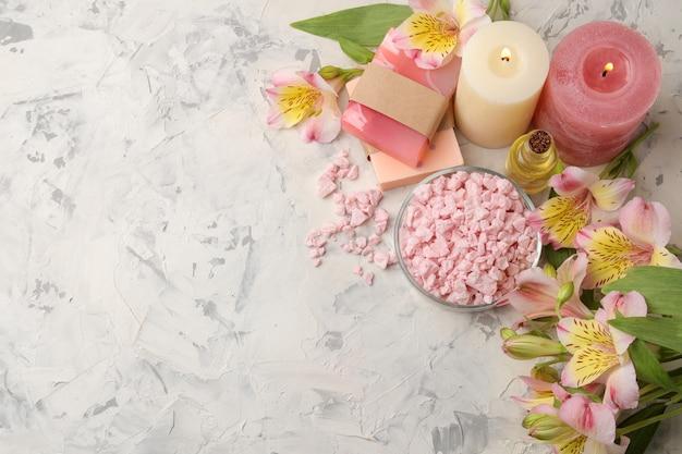 Spa compositie met zeezout, aroma oliën en handgemaakte zeep met bloemen op grijs en wit beton