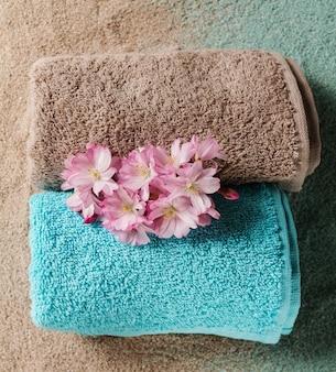 Spa concept. bovenaanzicht van prachtige spa-producten. mooie bloemen, handdoeken, spa zout, zand.
