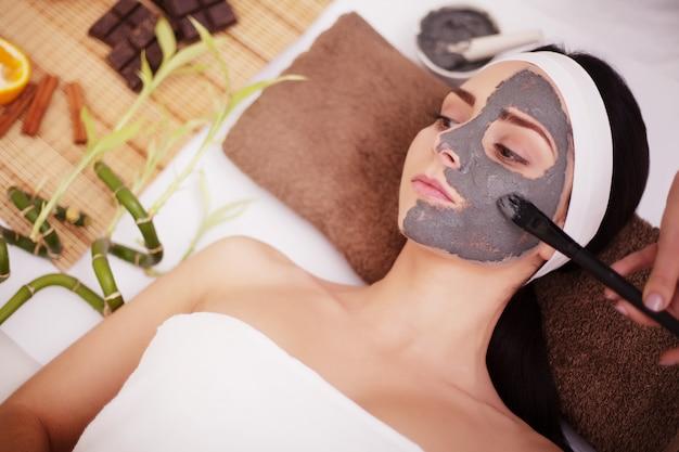 Spa concept. de jonge vrouw met voedingsstoffen gezichtsmasker in schoonheidssalon, sluit omhoog