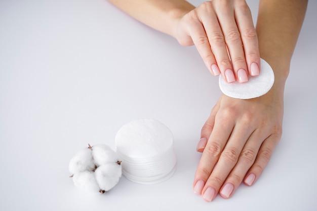 Spa concept. handen van een jonge vrouw met een katoenen schijf, witte katoenen bloem op een witte achtergrond. vrouwelijke manicure. katoenen bloem.