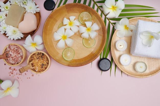 Spa concept. schoonheid en mode-concept met spa-set. geparfumeerd bloemenwater. ontspanning en zen, spa-omgeving plat met kom, badzout en bloemen, handdoek en natuurlijke zeep. bovenaanzicht.
