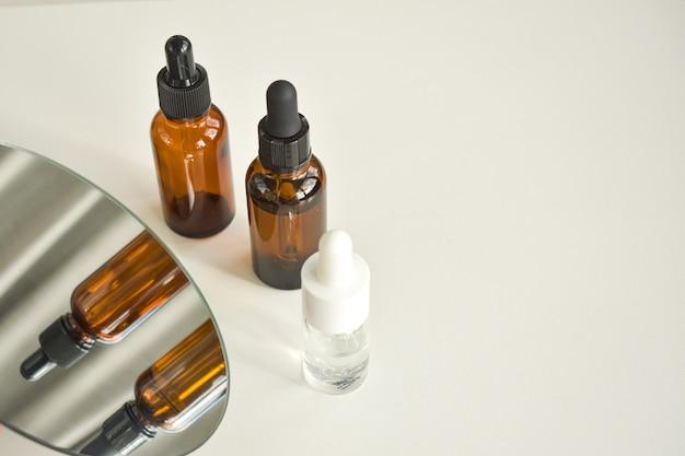 Spa cosmetica in bruine glazen flessen op een witte tafel.