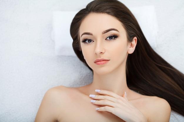Spa. de jonge mooie vrouw die op het bed met gelukkig kuuroordlichaam liggen en schrobt huid bij kuuroordsalon. concept van ontspannende gezondheid aroma spa, behandeling en lichaamsmassage