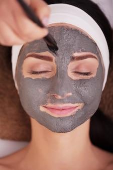 Spa. de jonge vrouw met voedingsstoffen gezichtsmasker in schoonheidssalon, sluit omhoog