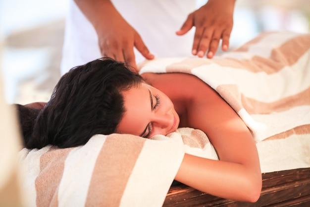 Spa en massage, mooie vrouw krijgt gezichts- en rugmassage op zonnig strand