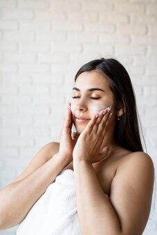Spa en schoonheid. gelukkige mooie kaukasische vrouw die badjassen draagt die gezichtscrème op haar gezicht toepassen