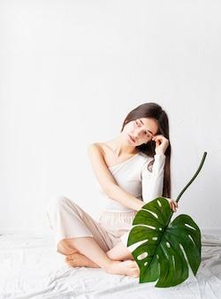Spa en schoonheid. zelfzorg en huidverzorging. gelukkig mooie vrouw in gezellige kleding met een groen monsterablad