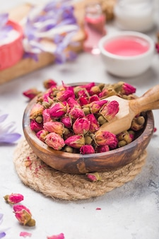 Spa en wellness-concept met droge rozen, roze olie en creame op concrete achtergrond.