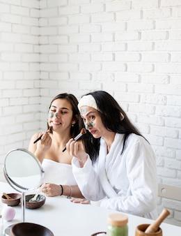 Spa- en wellness-concept. zelfzorg. twee mooie vrouwen die gezichtsmasker met plezier toepassen