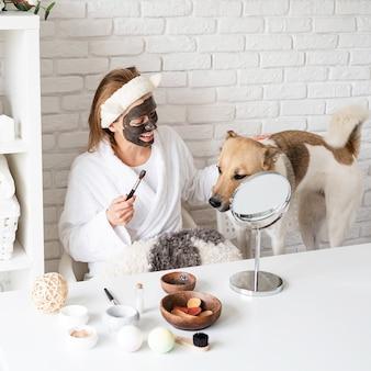 Spa en wellness. natuurlijke cosmetica. zelfzorg. jonge kaukasische vrouw die badjassen draagt die kuuroordprocedures met haar hond doen