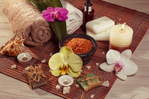 Spa- en wellness-omgeving met orchideebloemen, kom met zeezout, zeeschelp, fles met aromatische olie, zeep, kaarsen en handdoeken op bamboeservet