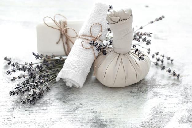 Spa- en wellnessomgeving met bloemen en handdoeken. heldere compositie met lavendelbloemen. dayspa natuurproducten met kokos