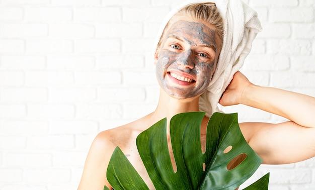 Spa gezichtsmasker. spa en schoonheid. gelukkige glimlachende vrouw die badhanddoeken met een gezichtsmasker van klei op haar gezicht draagt dat een groen monsterablad houdt