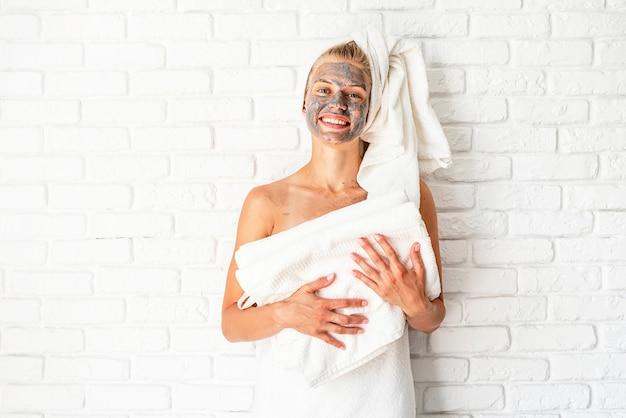 Spa gezichtsmasker. spa en schoonheid. jonge glimlachende vrouw die witte badhanddoeken met een gezichtsmasker van klei op haar gezicht houdt