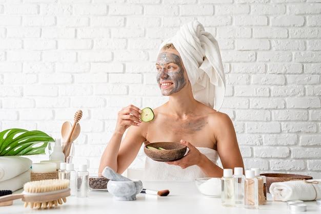 Spa gezichtsmasker. spa en schoonheid. jonge vrouw die witte handdoeken draagt die kuuroord gezichtsmasker op haar gezicht met een kosmetische borstel toepassen