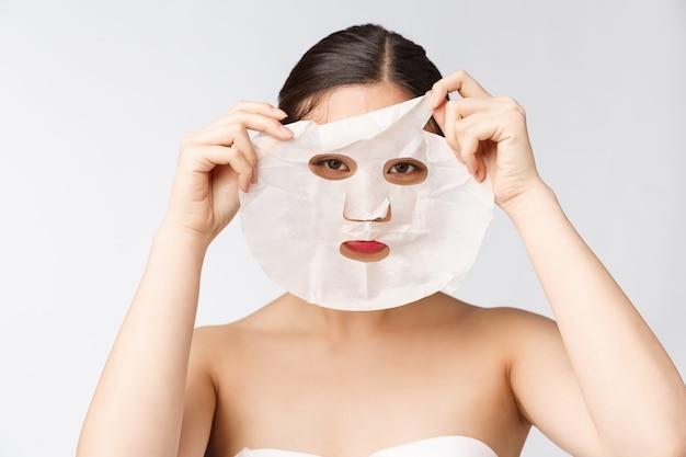 Spa, gezondheidszorg. vrouw met zuiverend masker op haar die gezicht op witte achtergrond wordt geïsoleerd.
