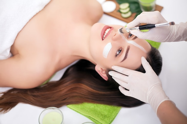 Spa. hand voedende masker op vrouwelijk gezicht in spa salon toe te passen