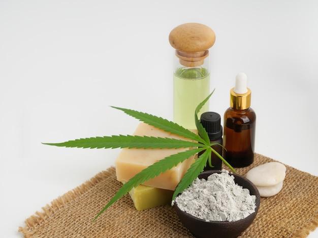 Spa hennep extract producten met cannabis blad zeep bar cbd olie lotion en modder masker op jute, zak op witte achtergrond