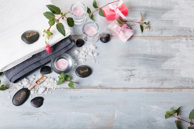 Spa-instelling op blauwe houten rustieke tafel. natuurlijk zeezout, kaarsen, handgemaakte zeep, bloemen, handdoeken. samenstelling van kuuroordtherapie, kuuroordconcept. bovenaanzicht