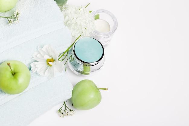 Spa-instelling op witte tafel. groene appels, handdoeken, kosmos bloemen en hortensia's, cosmetica, kaarsen. de therapiesamenstelling van het kuuroord, het concept van de kuuroordzomer. bovenaanzicht